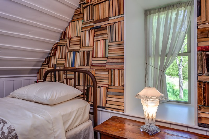Real books fill a wall in the loft bedroom.