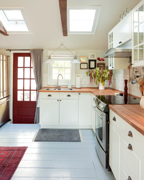 Butcher block counter tops and splashes of cherry red warm the new white kitchen. (Photo: Emily Gilbert)