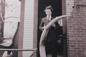Ernest Warther standing in front of his workshop with an ivory tusk. (Photo: Warther Museum)