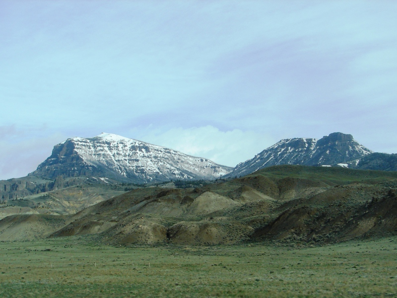 Snow-capped peaks of the Absaroka Range are the backdrop for rolling hills in Wapiti Valley.