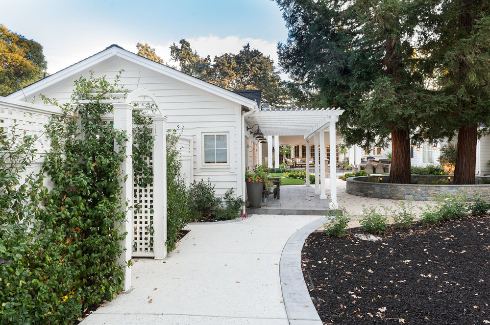 Another view of the guest house with privacy fence and vine-covered arbor. (Photo: Eric Shephard Architects)