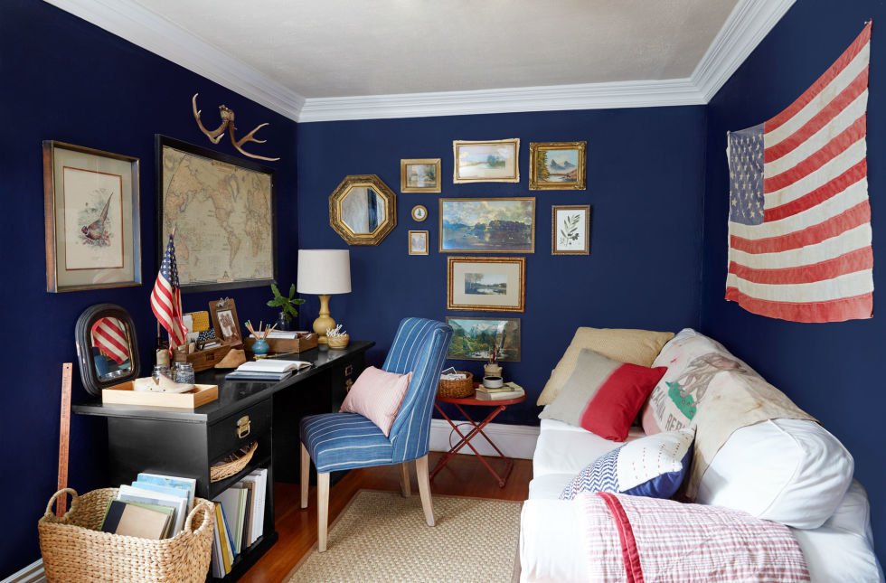 Vibrant navy walls, covered with carefully chosen treasures, warm the home office.