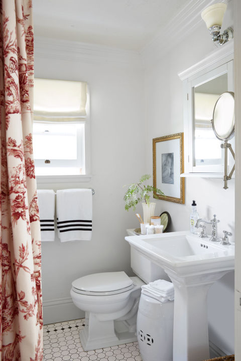 A toile curtain replaces the door in the small bathroom.
