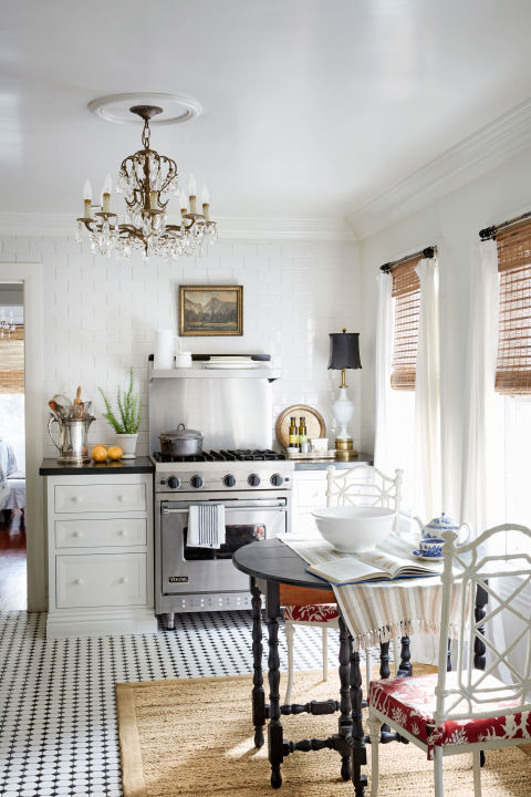 The kitchen is dressed with a chandelier, floor-length drapes, and vintage oil paintings.