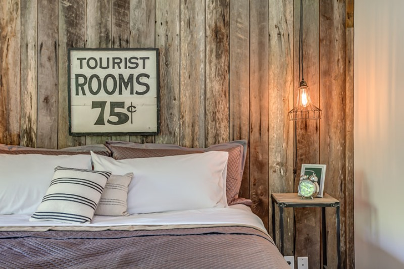 Distressed wood planks, industrial lighting, and a whimsical tourist sign.