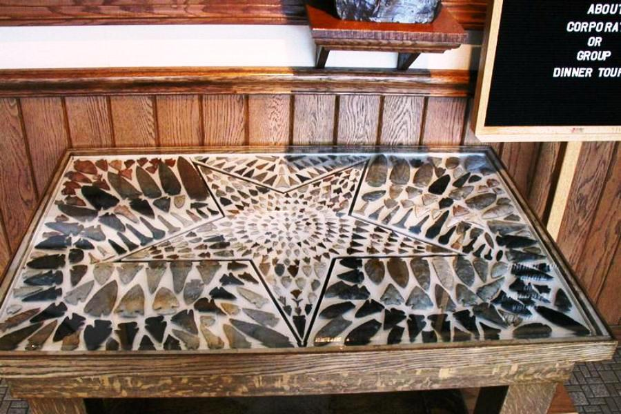 Case with arrowheads on display in museum lobby.