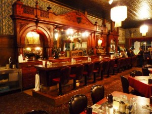 Irma Hotel's original cherry wood bar is ornate, exquisitely carved, and made from a single piece of wood. (Photo: Andrew Varga)