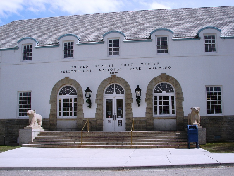 Mammoth Hot Springs' post office has understated classical architecture with a low hipped roof, rounded dormers, and two giant grizzlies flanking the front steps.