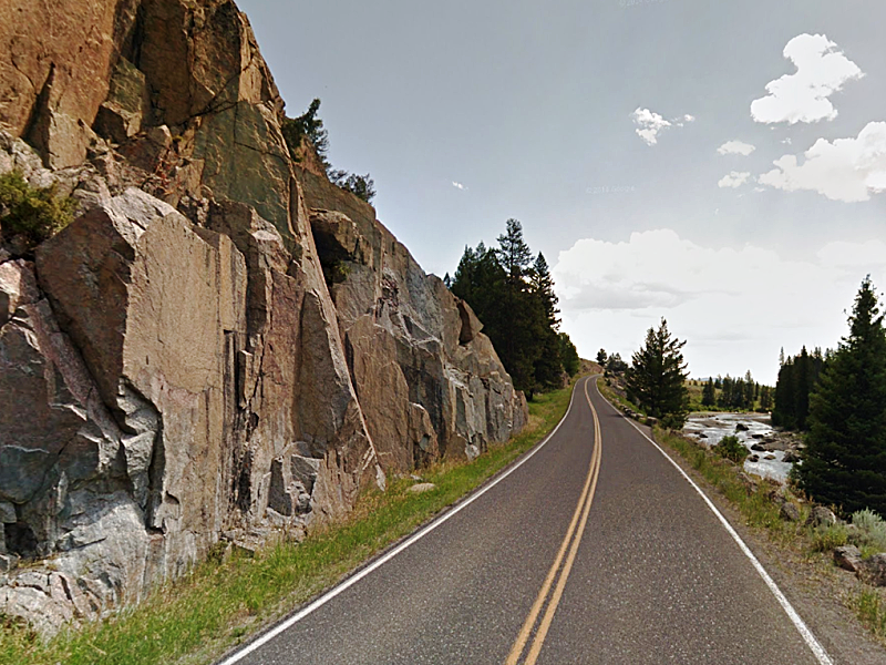 Grand Loop Road, flanked by tall rock and the Lamar River.