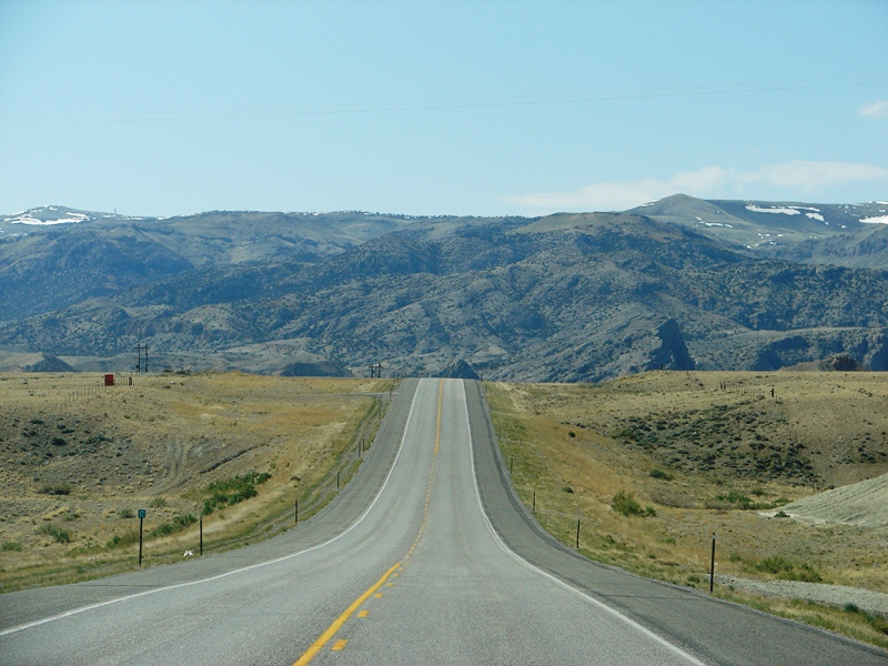 The Owl Creek Mountains at Wind River Canyon rise beyond the rise in the road.